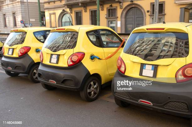 Electric car sharing station with cars being charged, on the street in downtown Milan, Italy