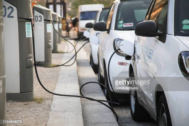 electric cars charging at a power station - hybrid vehicle stock pictures, royalty-free photos & images