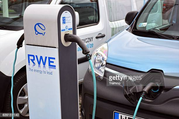 electric delivery van on the public charging point - power line stock photos and pictures