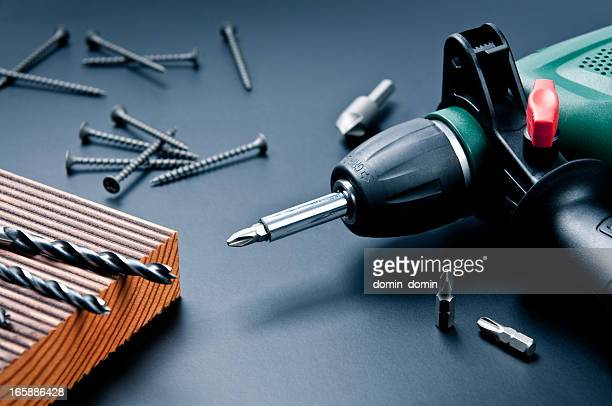 electric drill with drill bits, screws on dark background - drill stock pictures, royalty-free photos & images