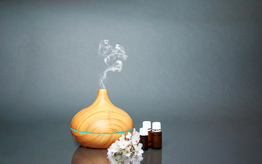 Electric Essential oils Aroma diffuser, oil bottles and flowers on gray surface with reflection. 951364696