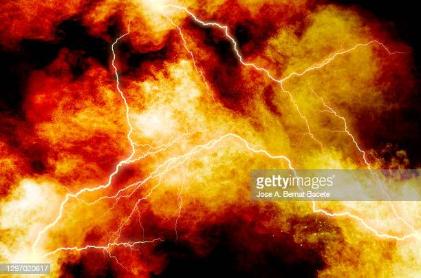 electric explosion of fire, smoke and sparks with lightning on a black background. - lightning stock pictures, royalty-free photos & images