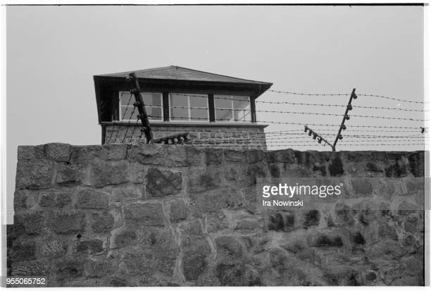 Electric fence and guard tower A guard tower rises above an electric stone fence at Mauthausen a Nazi concentration camp in operation during World...