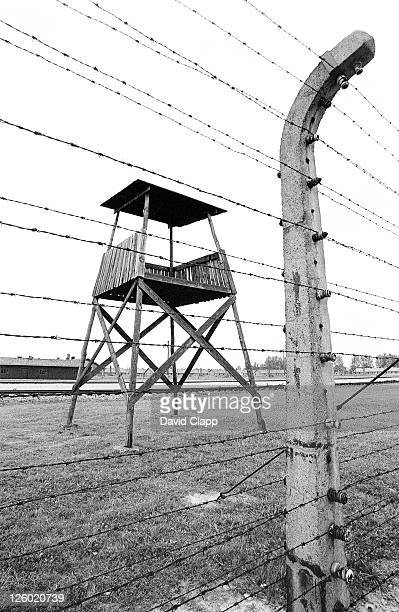 electric fence and lookout tower, birkenau concentration camp, auschwitz, poland - birkenau stock pictures, royalty-free photos & images