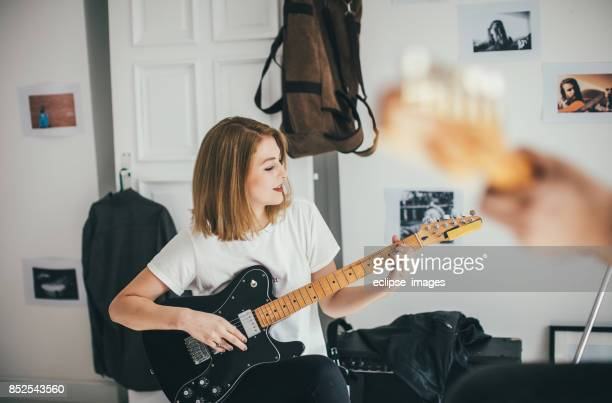 Electric guitar in hands of young woman