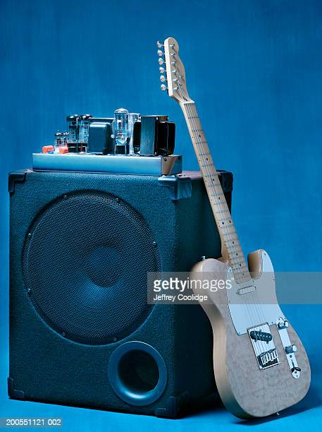 Electric guitar leaning on tube amplifier.