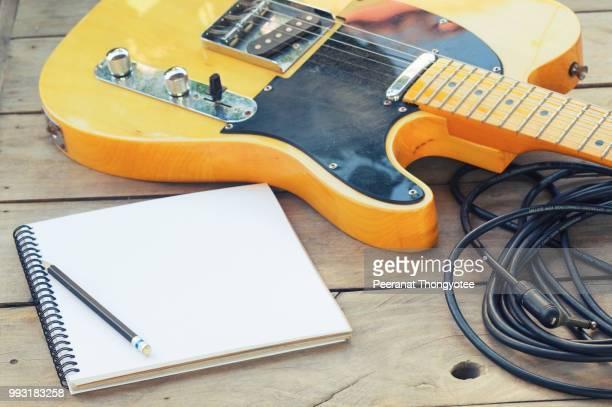 electric guitar on wood table - moderne rockmusik stock-fotos und bilder