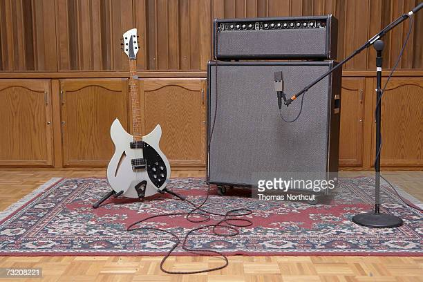 Electric guitar plugged into  amplifier and microphone in recording studio