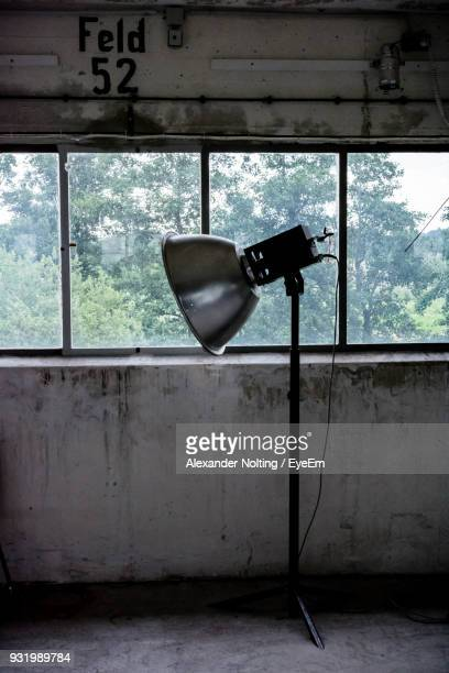 Electric Lamp In Abandoned Room Against Window
