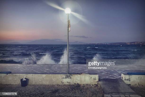 electric lamp on shoreline with breaking waves at sunset. - emreturanphoto stock pictures, royalty-free photos & images
