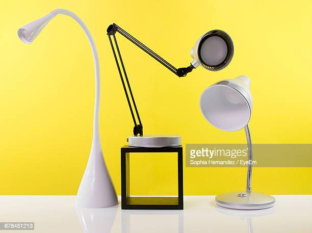 electric lamps on white table against yellow wall - small group of objects stock pictures, royalty-free photos & images