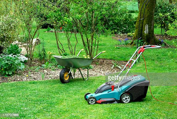 Electric Lawn Mower and Wheelbarrow in a Garden