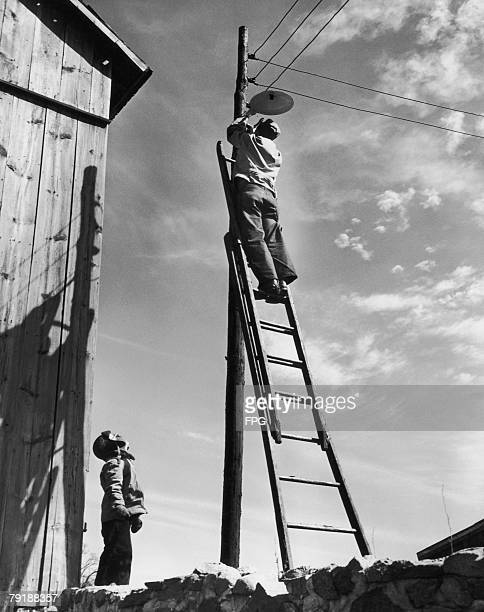 Electric lights being fitted on a farm circa 1935