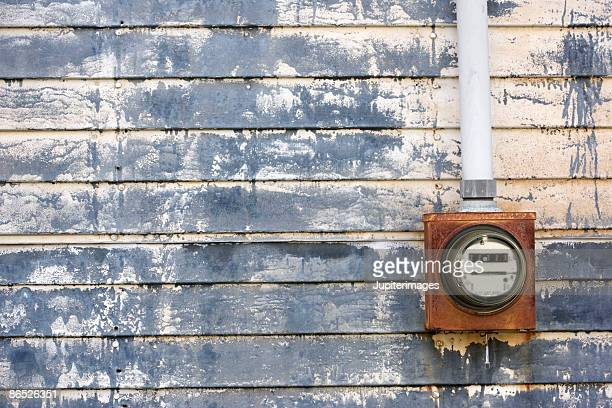 Electric meter on weathered urban wall
