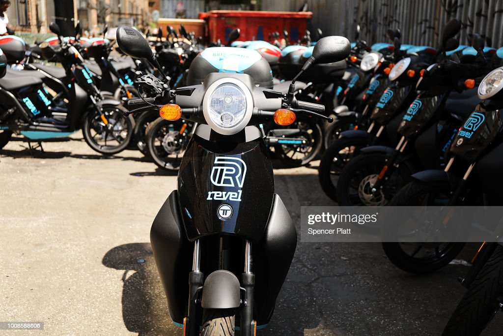 Electric mopeds operated by the company Revel sit parked in