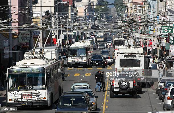 Electric MUNI buses make their way down Stockton Street February 2 2009 in the Chinatown District of San Francisco California A report by the San...