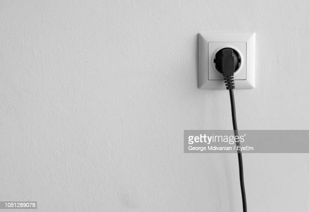 electric plug connected in outlet on white wall - tomada - fotografias e filmes do acervo