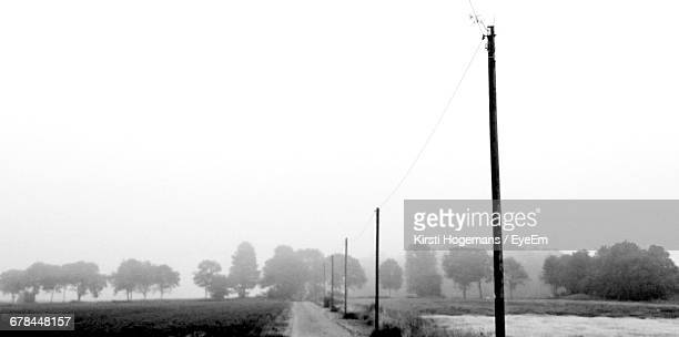 Electric Poles By Farm Against Clear Sky During Foggy Weather