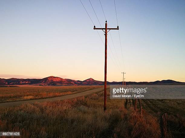 Electric Poles On Grassy Field Against Clear Sky During Sunset