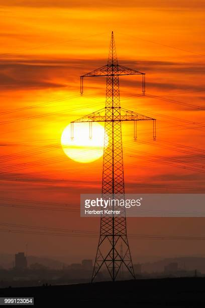 Electric power transmission lines, electricity pylon, with the setting sun, Beinstein near Stuttgart, Baden-Wuerttemberg, Germany