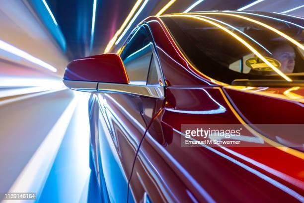 electric powered car drives on city street while night - unterwegs stock-fotos und bilder