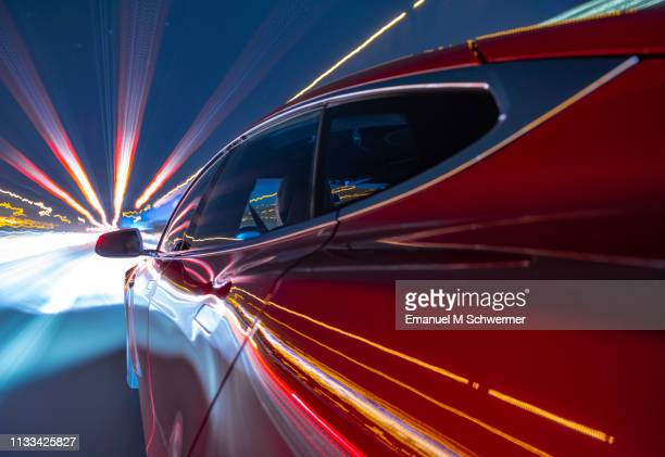 electric powered red car driving on german autobahn. - transportation stock pictures, royalty-free photos & images