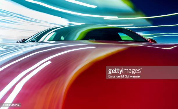 electric powered red driverless car drives through the blue night with streaking lights and reflections on the surface of the us car. - driverless car stock pictures, royalty-free photos & images