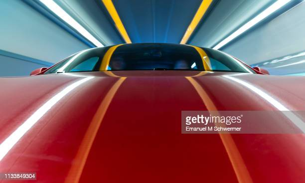 electric powered red us car drives through a tunnel - streaking lights on the hood of the car and surrounding. - transportmittel stock-fotos und bilder