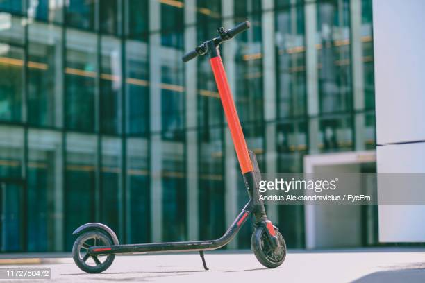 electric push scooter parked on footpath - electric scooter stock pictures, royalty-free photos & images