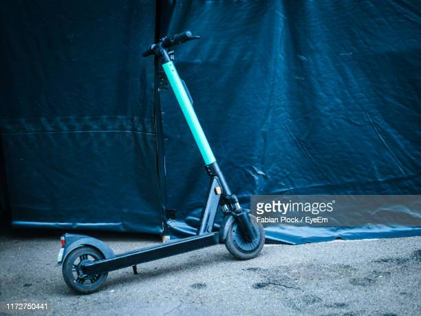 electric push scooter parked on road - sharing economy stock pictures, royalty-free photos & images