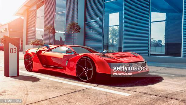 electric sports car gets power for batteries through charging station - charging sports stock pictures, royalty-free photos & images