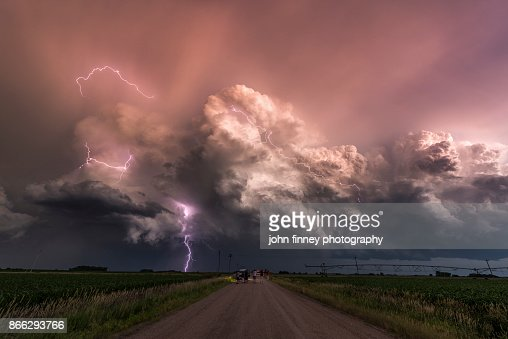 Electric storm at sunset watched by a group of storm chasers. USA