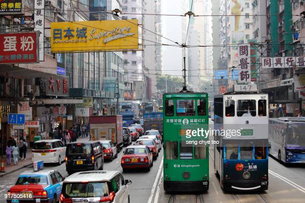 electric trams on a hong kong street - wanchai stock photos and pictures