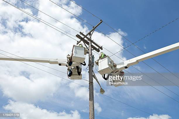 Electric Utility Workers in Truck Buckets near Pole