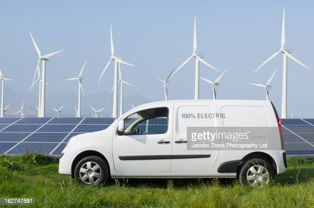 Electric van in front of solar panels and wind turbines