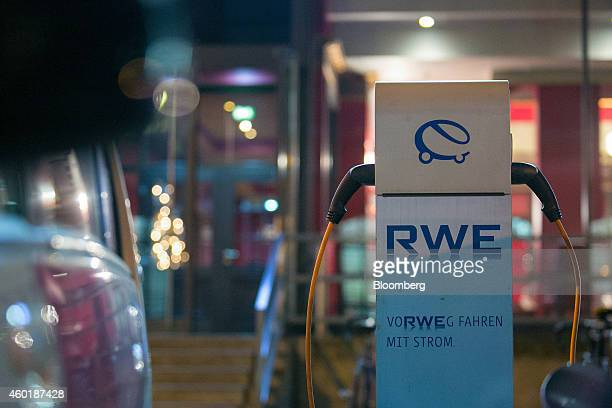 Electric vehicle charging plugs sit connected to an automobile charging station operated by RWE AG in Berlin Germany on Monday Dec 8 2014 Chancellor...