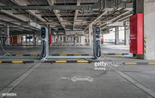 electric vehicle parking space and charging station - electric vehicle charging station stock photos and pictures