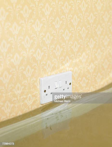 Electric wall outlet reflected in water in flooded living room