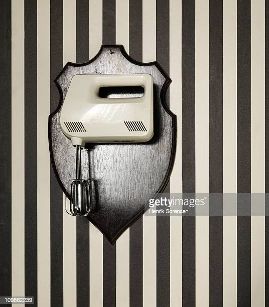 Electric whisk hanging as a trophy on a wall