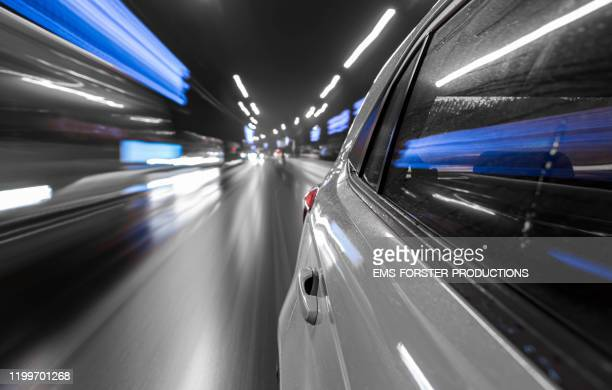 electric white car drives fast while rainy night in a city - rear view. - alternative fuel vehicle stock pictures, royalty-free photos & images