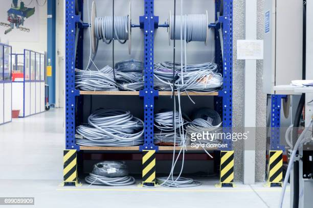 electrical cables on shelf in engineering plant - sigrid gombert stockfoto's en -beelden