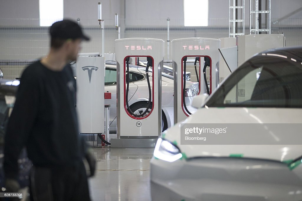 Electrical charging stations stand on the factory floor at the Tesla Motors Inc. electric automobile factory in Tilburg, Netherlands, on Friday, Dec. 9, 2016. A boom in electric vehicles made by the likes of Tesla could erode as much as 10 percent of global gasoline demand by 2035, according to the oil industry consultant Wood Mackenzie Ltd. Photographer: Jasper Juinen/Bloomberg via Getty Images