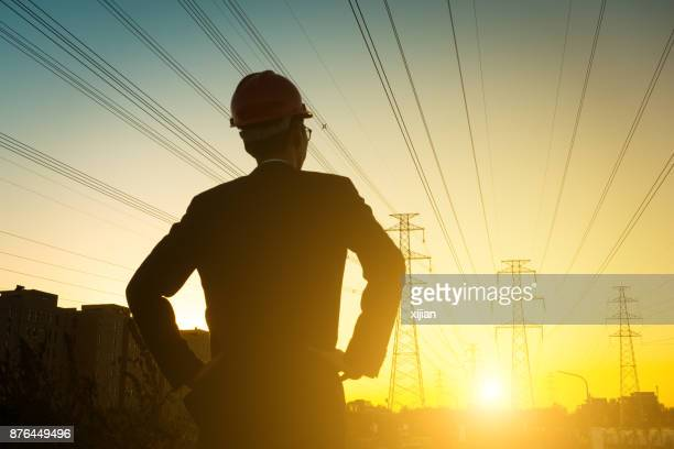 electrical engineer at sunset,back lit - electricity stock pictures, royalty-free photos & images