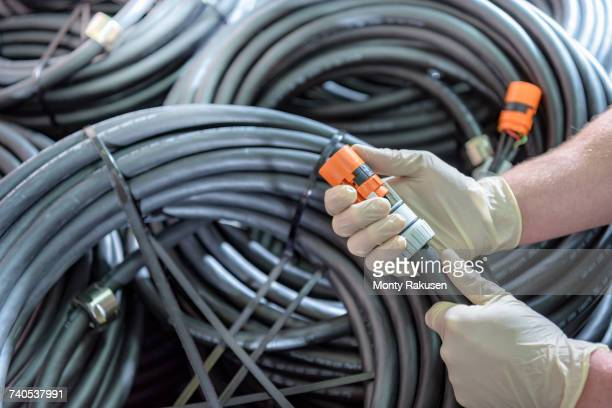 electrical engineer holding cables in cable finishing factory - monty rakusen stock pictures, royalty-free photos & images