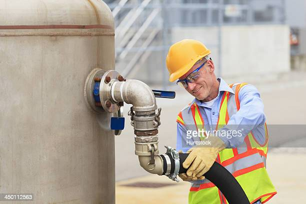 Electrical engineer inspecting hose connection for cooling supply lines at power plant