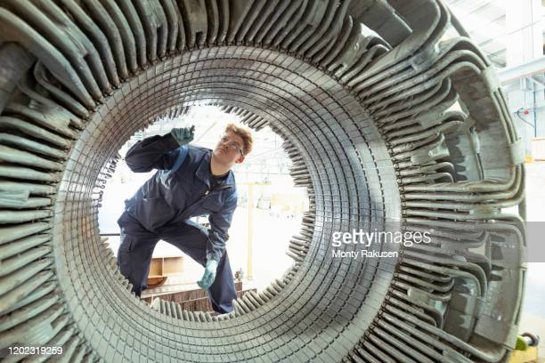 electrical engineer inspecting winding on generator stator in electrical engineering factory - generator stock pictures, royalty-free photos & images