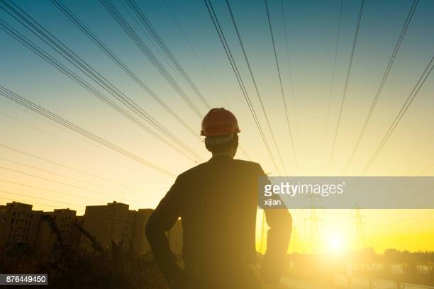 electrical engineer looking sunset - energy efficient stock photos and pictures