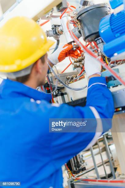 Electrical engineer setting up production line machine