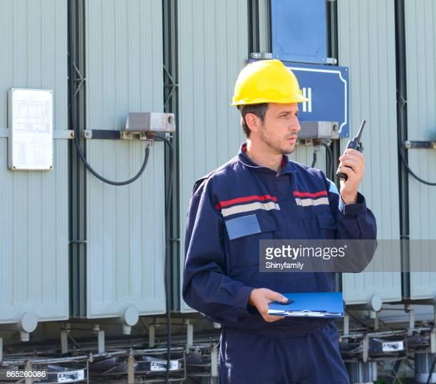 Electrical engineer working in power station near high voltage transformer