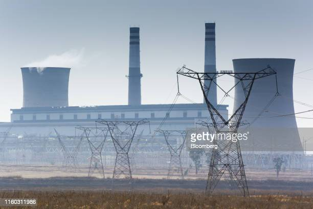 Electrical power lines hang from transmission pylons as the Eskom Holdings SOC Ltd. Grootvlei coal-fired power station stands beyond in Mpumalanga,...